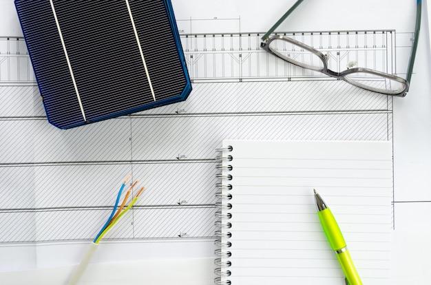 Vista dall'alto di celle solari, blocco note, penna, occhiali e cavo elettrico come concetto di pianificazione per il progetto fotovoltaico