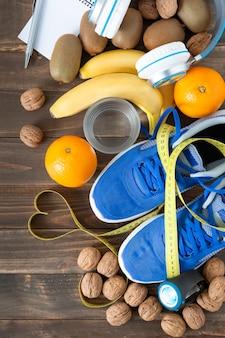 Vista dall'alto di alcuni cibi naturali, scarpe da ginnastica e metro a nastro su un tavolo di legno scuro. concetto di salute, cibo e sport.