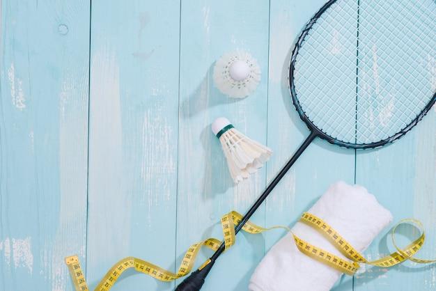 Vista dall'alto di attrezzature sportive, orologio, metro a nastro, scarpe, borraccia, asciugamano, racchetta da badminton e volano, stile di vita sano e concetto di fitness