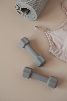 Vista dall'alto di sport, fitness, yoga, attrezzature per l'allenamento. tappetino, manubri, top su beige