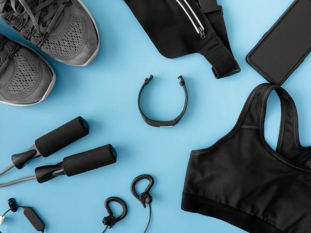 Vista dall'alto concetto di abbigliamento sportivo con attrezzatura da palestra, scarpe da corsa, smartphone e accessori per lo sport su sfondo blu con spazio di copia.