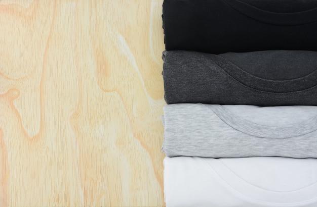 Pila vista dall'alto di maglietta monocromatica nera grigia e bianca arrotolata su sfondo di legno