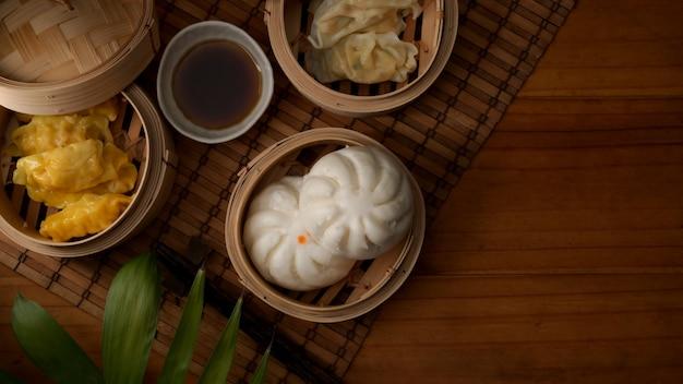 Vista superiore degli gnocchi cotti a vapore che servono sull'aggraffatrice di bambù con tè caldo sulla tavola di legno
