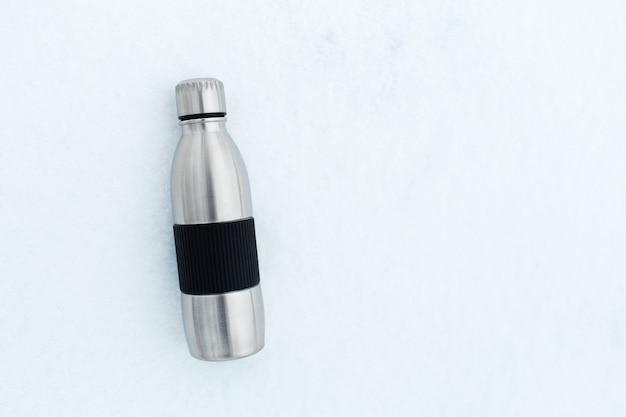 Vista dall'alto della bottiglia d'acqua termica riutilizzabile in acciaio sulla neve.