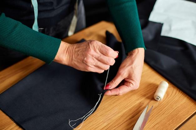 Vista dall'alto passo dopo passo, donna di 50 anni che cuce tessuto con la mano, sarto maturo che lavora con il cucito in atelier, industria tessile, hobby, spazio di lavoro.