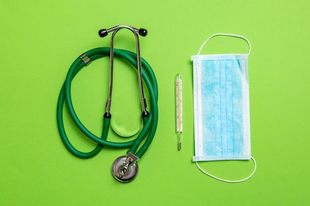 Vista dall'alto di uno stetoscopio, termometro a mercurio e una maschera protettiva sulla superficie colorata