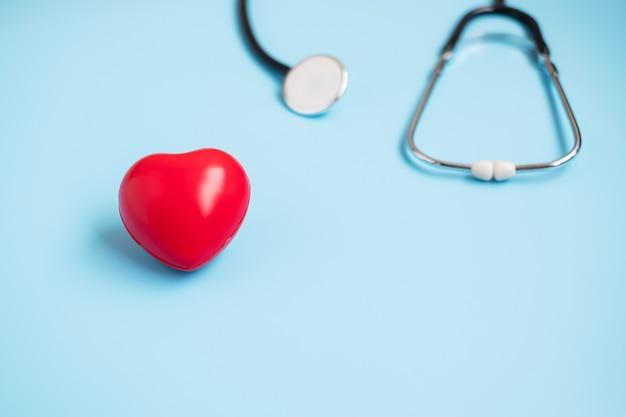 Stetoscopio vista dall'alto a forma di cuore rosso su sfondo blu con copia spazio per il testo. sanità, assicurazione sulla vita, giornata della salute, giornata mondiale del cuore e concetto di giornata del dottore felice