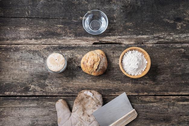 Vista dall'alto della natura morta con panino di pane a lievitazione naturale fatto in casa e ingredienti
