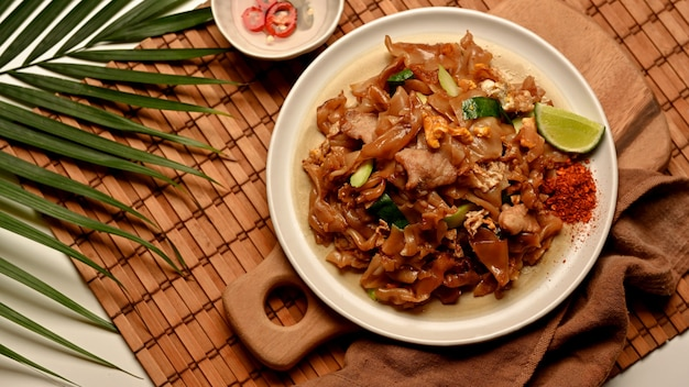 Vista dall'alto di noodle saltati in padella con salsa di soia dolce (pad see ew) con condimento su tovaglietta di bambù