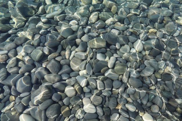 Vista dall'alto di pietre sotto l'acqua su acque poco profonde