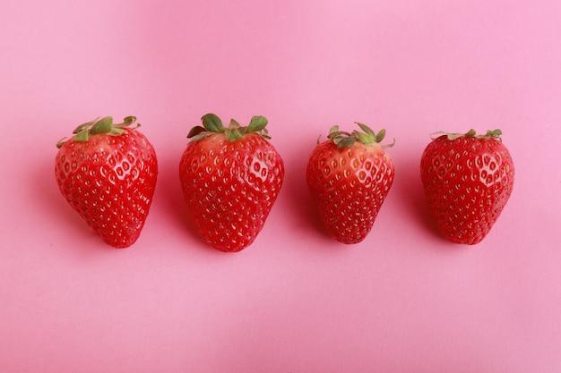 Vista dall'alto di fragole in fila su uno sfondo rosa