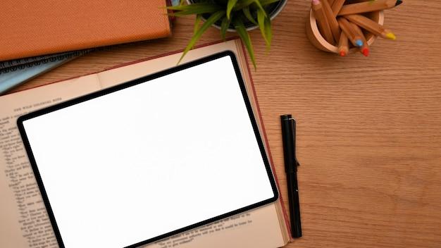 Vista dall'alto del tavolo di studio con il modello di schermo vuoto del computer tablet sul tavolo di legno