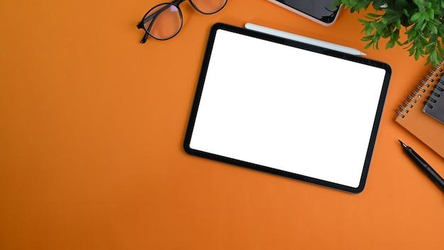Vista dall'alto di un'elegante area di lavoro con tablet digitale, notebook, occhiali e piante su sfondo arancione.