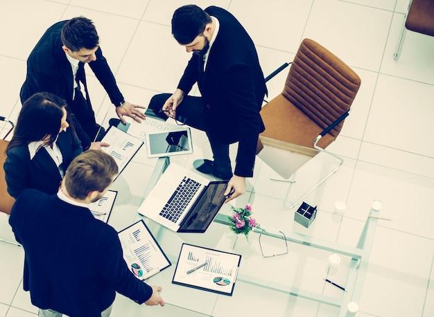 Vista dall'alto del team aziendale di successo che discute la grafica di marketing prima della riunione in un ufficio moderno.