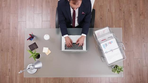 Vista dall'alto di un uomo d'affari di successo in tuta che digita la strategia di marketing sul laptop