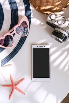 Vista superiore degli accessori e dello smart phone di estate sul fondo bianco di colore, concetto di viaggio.