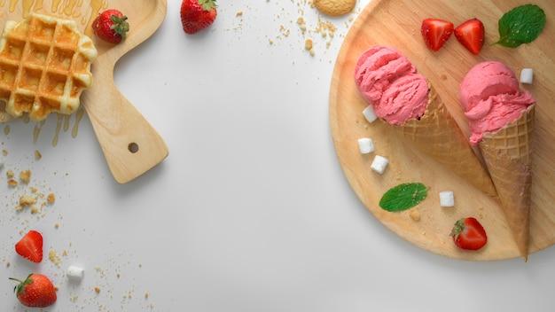 Vista dall'alto del dessert estivo con coni gelato alla fragola, cialde e topping