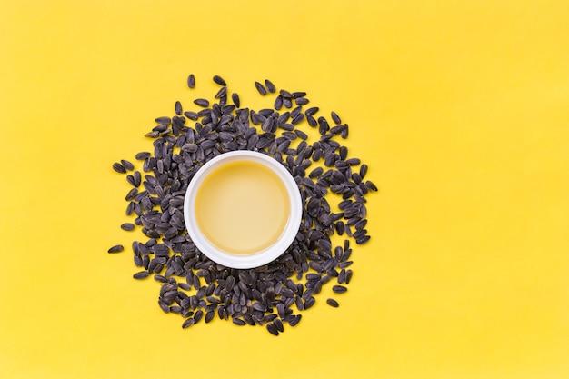 Vista dall'alto di semi di girasole e ciotola di olio, foto sopra la superficie gialla