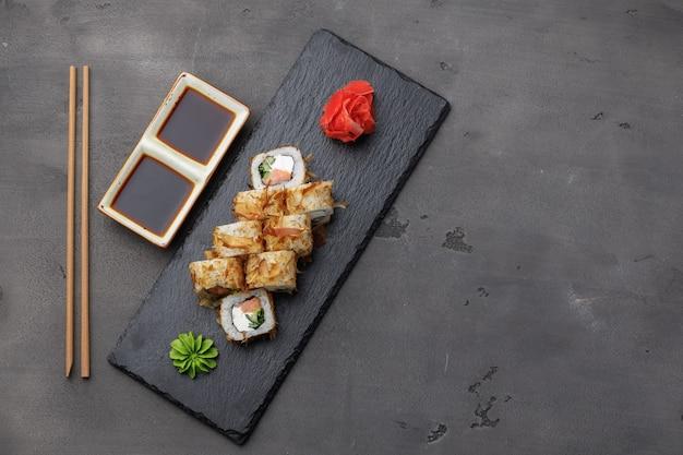 Vista dall'alto del rotolo di sushi con scaglie di tonno servito sul piatto