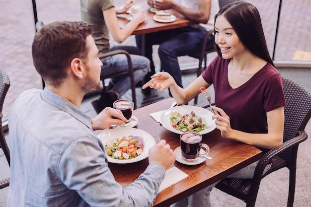 Vista dall'alto della dolce coppia entusiasta seduta al tavolo mentre bella donna che tiene forchetta e gesticolare