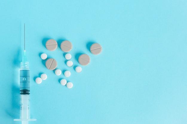 Vista dall'alto della siringa o dell'ago con la medicina della compressa isolata sull'azzurro