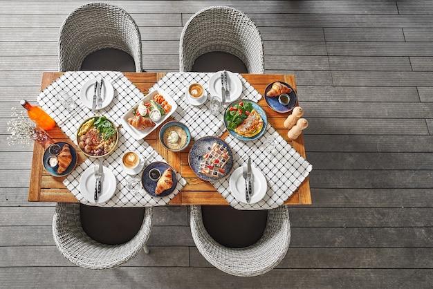 Vista dall'alto di un tavolo in un bar su una terrazza estiva, colazione o pranzo, in attesa degli ospiti. posto per il testo.