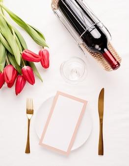 Vista dall'alto della tavola con carta menu, posate, tulipani rossi freschi e vino sulla tovaglia in tessuto bianco
