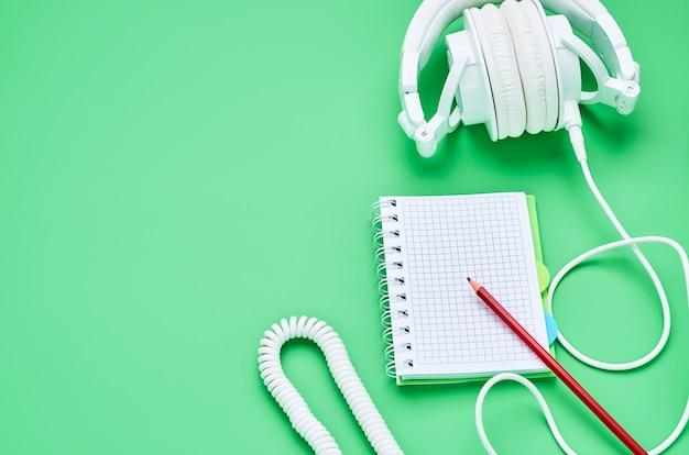 Vista superiore della tabella di un bambino adolescente, matita del taccuino delle cuffie della composizione su fondo verde chiaro