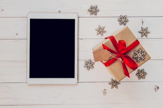 Tabella di vista superiore, e confezione regalo con fiocchi di neve su sfondo bianco di legno per natale e nuovo anno. natale e capodanno concetto.