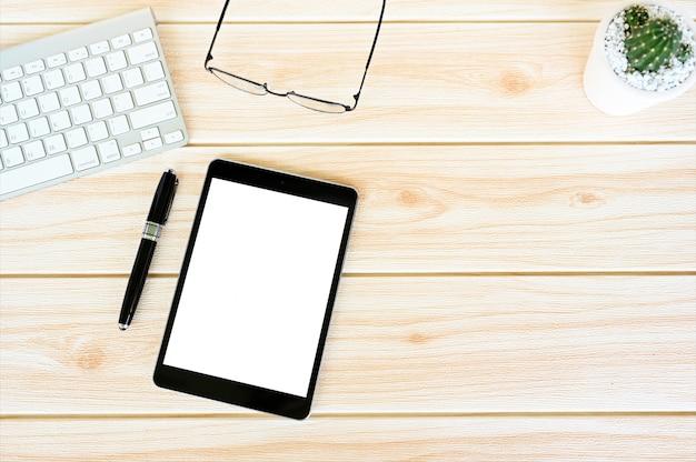Vista dall'alto schermo del tablet, penna, laptop e piante verdi sulla scrivania bianca copia spazio