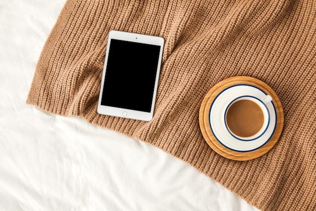Vista dall'alto di un tablet con una tazza di caffè su un maglione sulle lenzuola