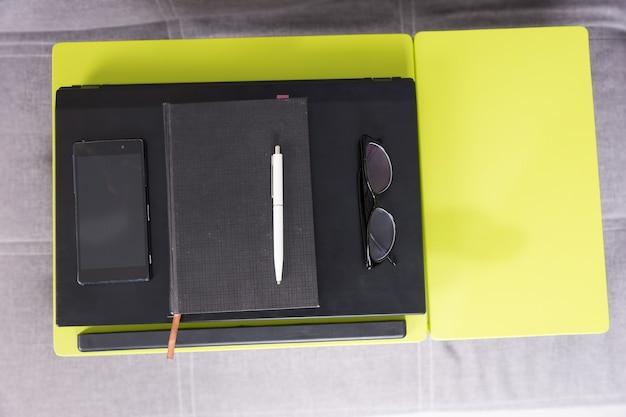 La vista dall'alto di una workstation da tavolo con laptop chiuso, un diario, occhiali e telefono cellulare sono disposti in ordine rigoroso su di essa