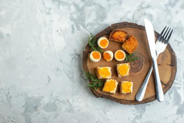 Vista dall'alto gustosi panini al caviale con uova sode e posate su tavola di legno superficie bianca colazione pranzo pesce pesce toast