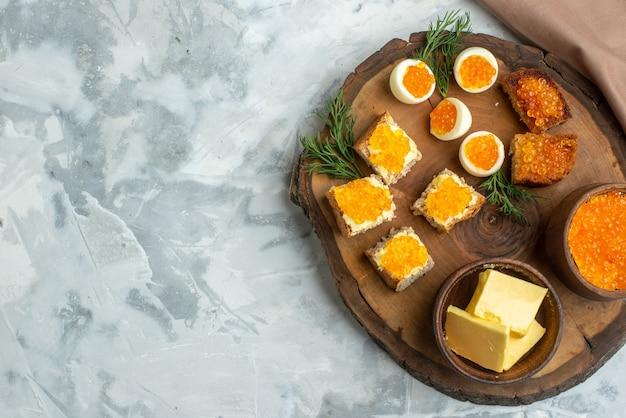 Vista dall'alto gustosi panini al caviale con uova sode su tavola di legno sfondo bianco colazione pranzo toast cibo pasto frutti di mare pesce spazio libero