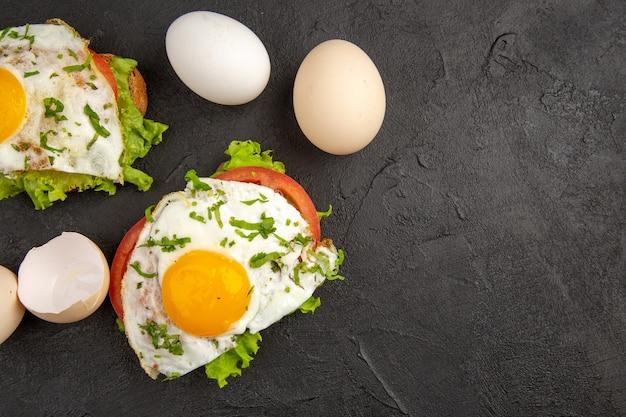 Vista dall'alto gustosi panini all'uovo con uova fresche su sfondo scuro bollire il pasto colazione cibo frittata pane all'uovo pranzo spazio libero