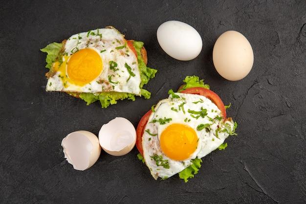 Vista dall'alto gustosi panini all'uovo con uova fresche su sfondo scuro far bollire il pasto colazione cibo frittata pane all'uovo pranzo