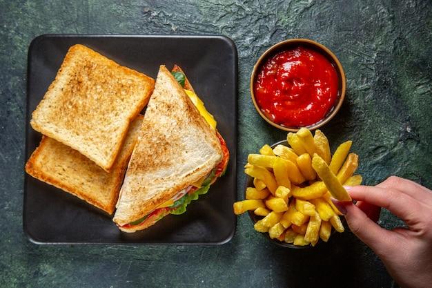 Vista dall'alto gustosi panini al prosciutto con toast patatine fritte e concentrato di pomodoro sulla superficie scura