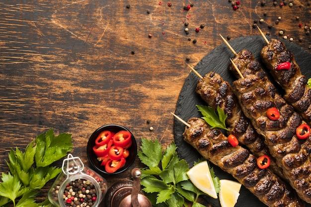 Vista dall'alto di gustosi kebab sulla piastra con erbe e spazio di copia