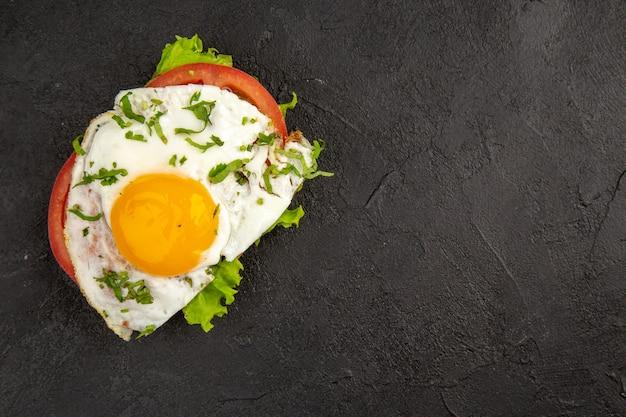 Vista dall'alto gustoso panino con uova e pomodori su sfondo scuro pasto uovo colazione pranzo cibo frittata bollire il pane spazio libero per il testo