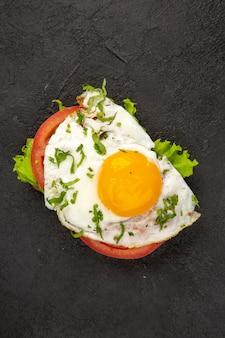 Vista dall'alto gustoso panino con uova e pomodori su sfondo scuro pasto uovo colazione pranzo cibo frittata bollire il pane