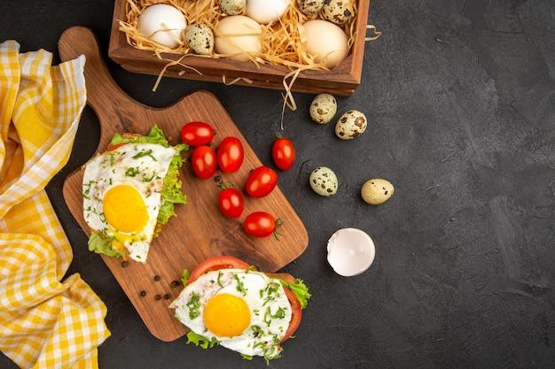 Vista dall'alto gustosi panini con uova e pomodori su sfondo scuro pasto uovo colazione pane pranzo cibo frittata bollire spazio libero