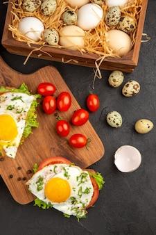 Vista dall'alto gustosi panini con uova e pomodori su sfondo scuro pasto uovo colazione pane pranzo cibo frittata bollire