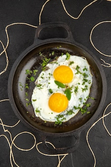 Vista dall'alto gustose uova strapazzate con verdure all'interno della padella su sfondo scuro colazione pane pasto mattina frittata tè
