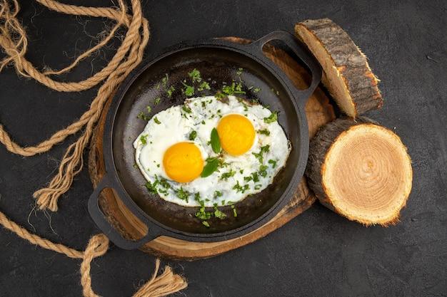 Vista dall'alto gustose uova strapazzate con verdure all'interno della padella su sfondo grigio tè colazione pane cibo pasto mattina frittata pranzo bollire