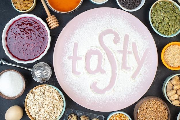 Vista dall'alto gustosa scritta farina con noci semi cereali uvetta e gelatina su sfondo scuro torta colazione cibo pasta torta polvere cuocere