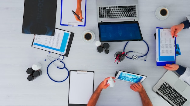 Vista dall'alto dei medici del team sul tavolo della scrivania con stetoscopio e dispositivi digitali durante la conferenza