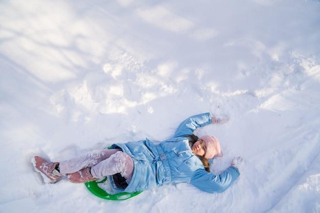 Vista dall'alto una ragazza adolescente con un cappello rosa e un cappotto blu cerca di muoversi su una slitta verde da uno scivolo di neve, ma la neve è molta e non scivola e cade. passeggiate invernali per bambini. vestiti per il gelo