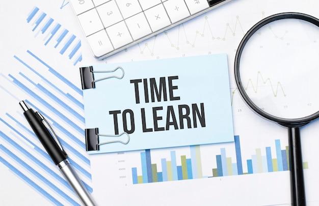 Vista dall'alto del testo time to learn con calcolatrice, lente d'ingrandimento e penna sui grafici finanziari