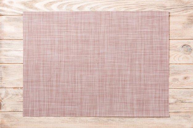Vista superiore della stuoia marrone del tessuto per la cena su fondo di legno con lo spazio della copia