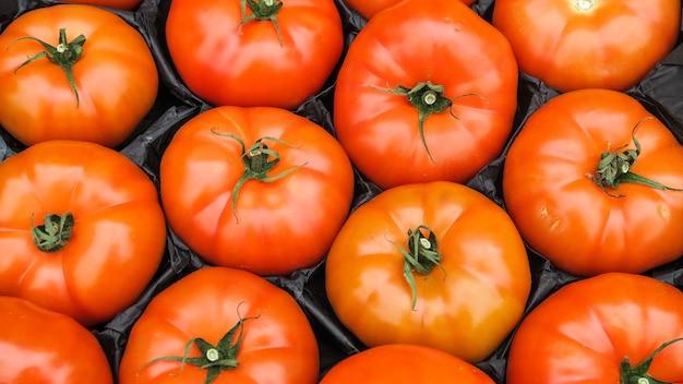 La struttura di vista superiore dei pomodori rossi ha messo dentro la scatola pronta a vendere nel mercato locale, fondo